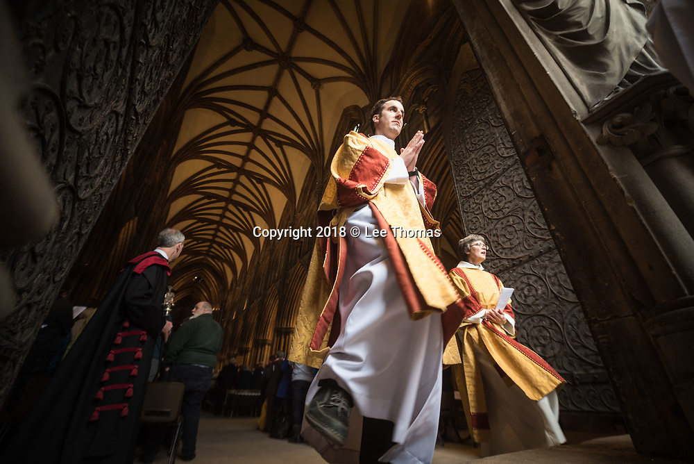 Lichfield Cathedral, Lichfield, Staffordshire, UK. 29th March 2018. The Bishop of Lichfield together with hundreds of clergy and worshippers join together at Lichfield Cathedral to commemorate Maundy Thursday. Pictured: Members of the clegy step out of the Great West doors at Lichfield Cathedral after the Maundy Thursday service. // Lee Thomas, Tel. 07784142973. Email: leepthomas@gmail.com  www.leept.co.uk (0000635435)