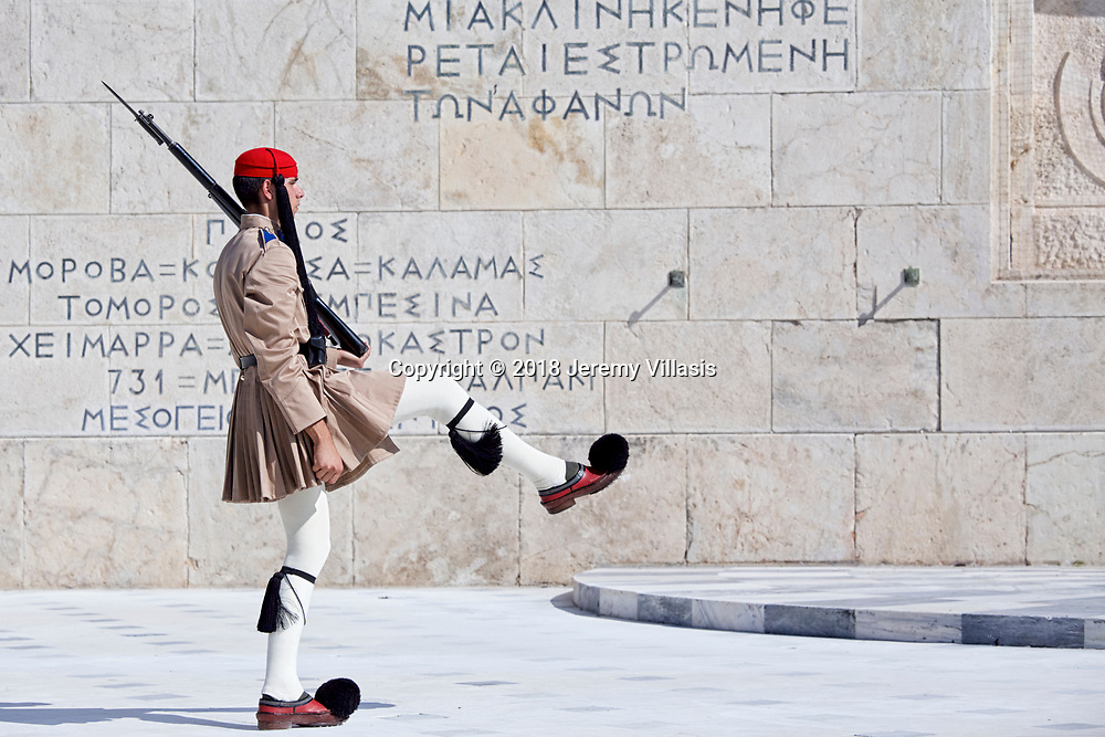 An Evzones of the Presidential Guard marches during the changing of the guard ceremony at the war memorial of the Tomb of the Unknown Soldier in the heart of modern Athens, Greece.