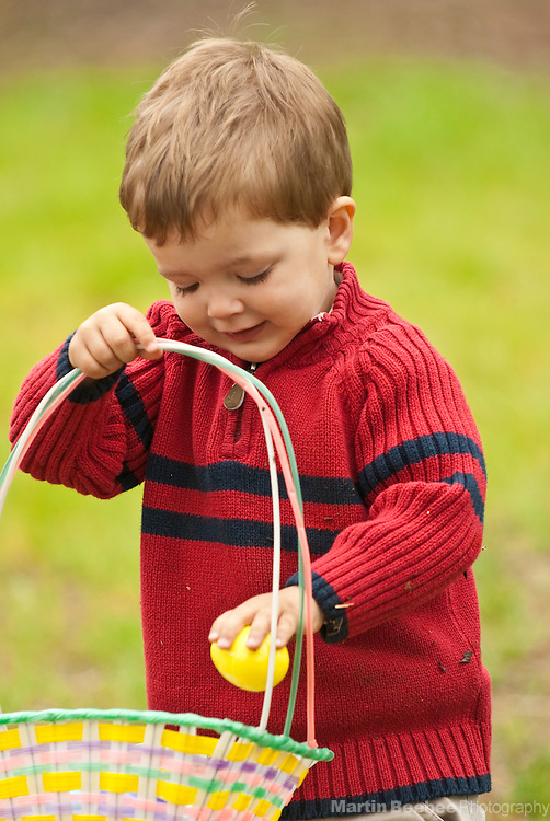 A two-year-old boy collects Easter eggs with his basket on Easter Sunday