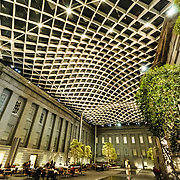 The interior of the Robert and Arlene Kogod Courtyard in the center of the Smithsonian's David W. Reynolds Center for American Art and Portraiture in downtown Washington DC. This shot, at night, shows the dark night sky through the glass ceiling.