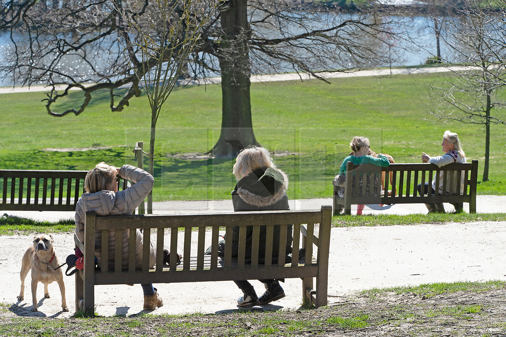 ©Licensed to London News Pictures 23/03/2020<br /> Tunbridge Wells, UK. Ladies chatting from each end of a park bench. A very quiet Dunorlan park in Royal Tunbridge Wells, Kent this afternoon as people seem to be following the Coronavirus advice of Social distancing. Photo credit: Grant Falvey/LNP