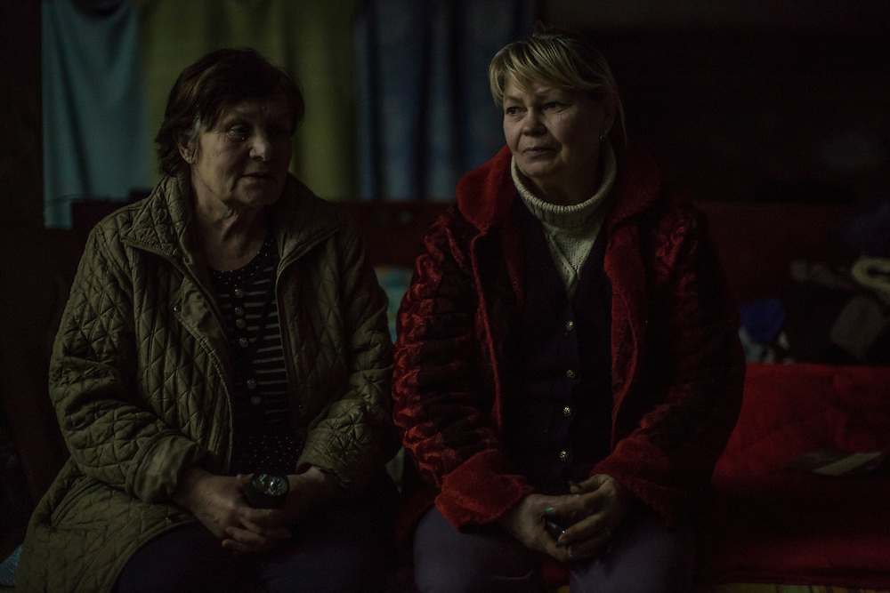 DONETSK, UKRAINE - JANUARY 29, 2015: Zina Yesikova, left, and Lilia Motruk sit in the dark during a power outage in an underground bomb shelter in the Petrovskyi district of Donetsk, Ukraine. The neighborhood has been shelled heavily in the past few days, forcing many people back to the shelters they first fled to in the summer. CREDIT: Brendan Hoffman for The New York Times