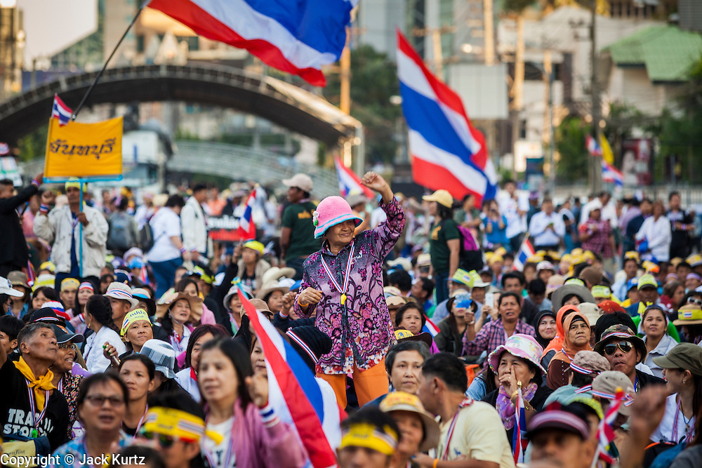 "13 JANUARY 2014 - BANGKOK, THAILAND: A woman dances and cheers during an anti-government rally in the Asoke intersection in Bangkok. Tens of thousands of Thai anti-government protestors took to the streets of Bangkok Monday to shut down the Thai capitol. The protest was called ""Shutdown Bangkok"" and is expected to last at least a week. The Shutdown Bangkok protest is a continuation of protests that started in early November. There have been shootings almost every night at different protests sites around Bangkok, including two Sunday night, but the protests Monday were peaceful. The malls in Bangkok stayed open Monday but many other businesses closed for the day and mass transit was swamped with both protestors and people who had to use mass transit because the roads were blocked.    PHOTO BY JACK KURTZ"