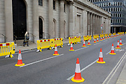 As the UK's Conornavirus pandemic lockdown continues, but with travel restrictions and social distancing rules starting to ease after three months of closures and isolation, Londoners pass yellow barriers and social distance cones which have narrowed the road in favour of wider pedestrian pavements outside the Bank of England on Threadneedle Street, on 9th June 2020, in London, England.