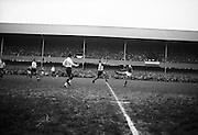 Irish full back Kiernan kicks right footed for touch near Irish goal with Pique in close attendance,..Irish Rugby Football Union, Ireland v France, Five Nations, Landsdowne Road, Dublin, Ireland, Saturday 23rd January, 1965,.23.1.1965, 1.23.1965,..Referee- D G Walters, Welsh Rugby Union, ..Score- Ireland 3 - 3 France, ..Irish Team, ..T J Kiernan,  Wearing number 15 Irish jersey, Full Back, Cork Constitution Rugby Football Club, Cork, Ireland,..P J Casey, Wearing number 14 Irish jersey, Right Wing, Landsdowne Rugby Football Club, Dublin, Ireland, ..J C Walsh,  Wearing number 13 Irish jersey, Right Centre, University college Cork Rugby Football Club, Cork, Ireland,..M K Flynn, Wearing number 12 Irish jersey, Left Centre, Wanderers Rugby Football Club, Dublin, Ireland, ..K J Houston, Wearing number 11 Irish jersey, Left Wing, Bruff Rugby Football Club, Limerick, Ireland, and, Oxford University Rugby Footabll Club, Oxford, England, ..C M H Gibson, Wearing number 10 Irish jersey, Stand Off, Cambridge University Rugby Football Club, Cambridge, England, and, N.I.F.C, Rugby Football Club, Belfast, Northern Ireland, ..R M Young, Wearing number 9 Irish jersey, Scrum Half, Queens University Rugby Football Club, Belfast, Northern Ireland,..S MacHale, Wearing number 1 Irish jersey, Forward, Landsdowne Rugby Football Club, Dublin, Ireland, ..K W Kennedy, Wearing number 2 Irish jersey, Forward, Queens University Rugby Football Club, Belfast, Northern Ireland,..R J McLoughlin, Wearing number 3 Irish jersey, Captain of the Irish team, Forward, Gosforth Rugby Football Club, Newcastle, England, ..W J McBride, Wearing number 4 Irish jersey, Forward, Ballymena Rugby Football Club, Antrim, Northern Ireland,..W A Mulcahy, Wearing number 5 Irish jersey, Forward, Bective Rangers Rugby Football Club, Dublin, Ireland, ..M G Doyle, Wearing number 6 Irish jersey, Forward, University College Dublin Rugby Football Club, Dublin, Ireland,..R A Lamont, Wearing number 8 Irish jersey, Forward, Instoni