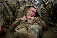 While waiting for the plane to arrive, Specialist Joseph Colona sleeps with luggage after the deployment ceremony for the California Army National Guard&rsquo;s 1st Battalion, 184th Infantry Regiment, at the International Jet Center at Sacramento Airport,  Saturday Sep 16, 2017. About 300 Soldiers from the California Army National Guard&rsquo;s 1st Battalion, 184th Infantry Regiment, will depart California this weekend for a yearlong training deployment to Jordan in the Middle East. <br /> photo by Brian Baer
