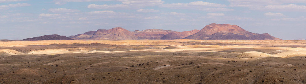 Mountains of red granite rich in sandstone turn to blood in the dappled afternoon light, Namibia.