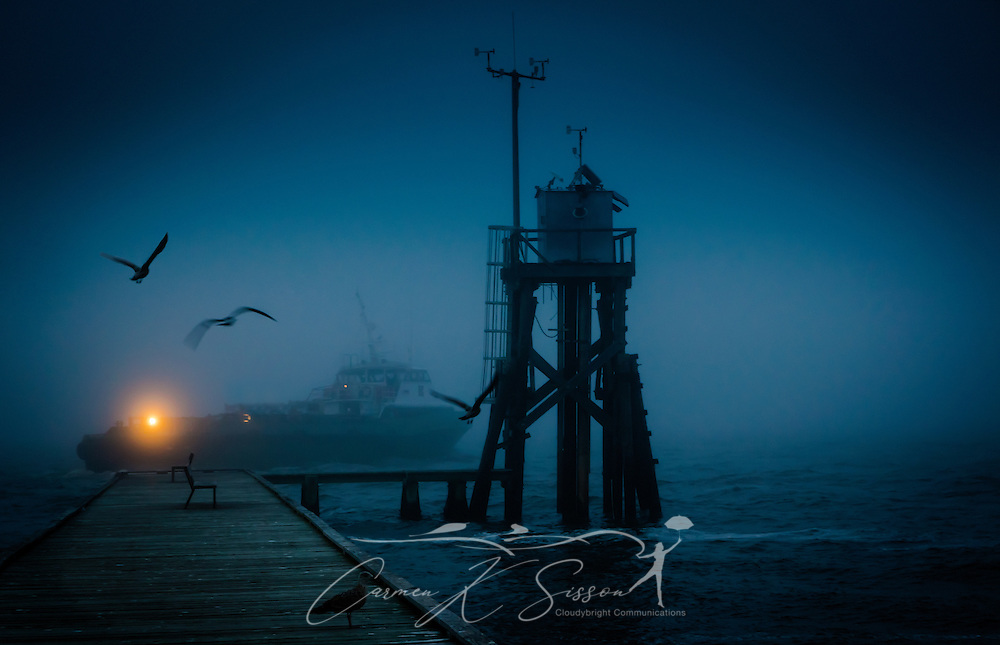A boat passes a wharf on a foggy evening near Fort Gaines in Dauphin Island, Alabama, Feb. 20, 2014. (Photo by Carmen K. Sisson/Cloudybright)