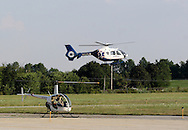 Montgomery, NY - A pilot gets ready to take off in his Robinson R22 Beta helicopter as a LlifeNet emergency helicopter flies by in the background at Orange County Airport on July 26, 2008.