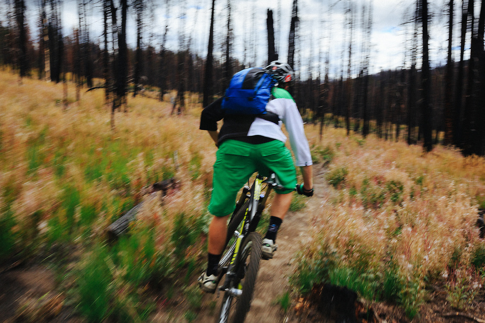 Andrew Whiteford rides through a wildfire burn that crossed singletrack in Jackson, Wyoming.