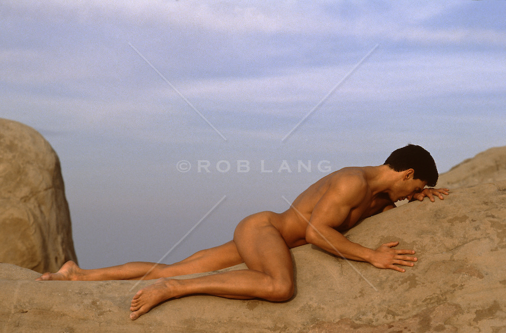 nude muscular man on a rock formation