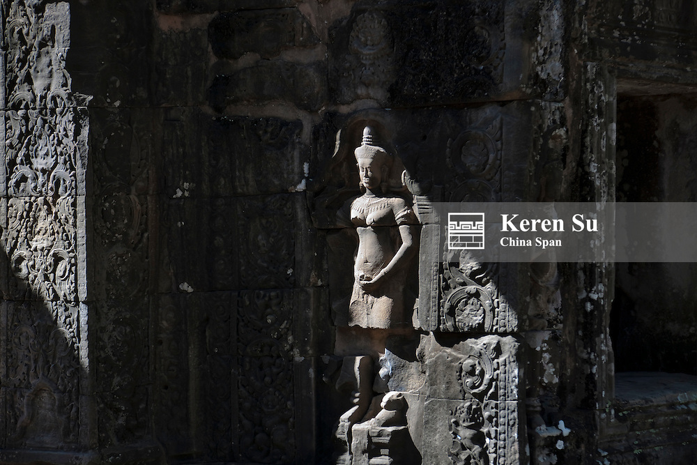 Monk with Buddhist statues in Banteay Kdei, UNESCO World Heritage site.