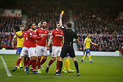 Referee Darren England shows a yellow card to Nottingham Forest defender Jack Robinson (18)  during the EFL Sky Bet Championship match between Nottingham Forest and Leeds United at the City Ground, Nottingham, England on 1 January 2019.