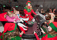 Santa's Elves Garland, Snowy and Crinkle give Maddie Isabelle, Catherine and Alexandra Fay and Kali Muzzey a magical ride in Santa's sleigh during opening night of the annual Christmas Village Thursday.  (Karen Bobotas/for the Laconia Daily Sun)