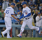 Los Angeles Dodgers third base coach Chris Woodward #45 congratulaes Los Angeles Dodgers catcher Yasmani Grandal #9 on his solo homer in the 5h inning. The Los Angeles Dodgers played the Cincinnati Reds at Dodger Stadium in Los Angeles , CA.  May 25, 2016. (Photo by John McCoy/Southern California News Group