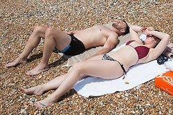 © Licensed to London News Pictures. 29/05/2016. Brighton, UK. Leah and Shaun Wilmer take a break during their weekend trip to Brighton for some sunbathing on the beach. Photo credit: Hugo Michiels/LNP