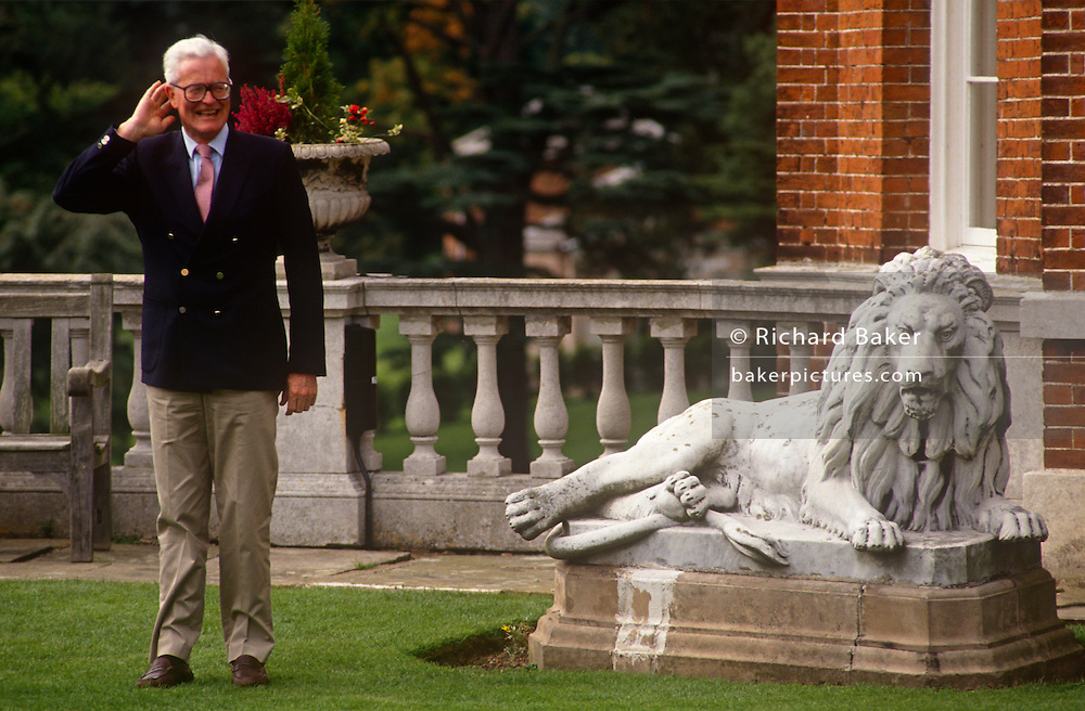 Douglas Hurd MP strains to listen to reporters, standing next to a lion statuette while hosting a foreign ministers' summit in the summer of 1990 at Dorneywood, England. Douglas Richard Hurd, Baron Hurd of Westwell, CH, CBE, PC (b1930) is a British Conservative politician who served in the governments of Margaret Thatcher and John Major from 1979 to 1995.