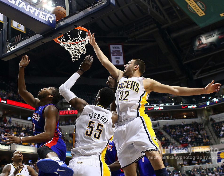 Feb. 23, 2011; Indianapolis, IN, USA; Detroit Pistons power forward Greg Monroe (10) puts up the shot as Indiana Pacers center Roy Hibbert (55) and Indiana Pacers forward Josh McRoberts (32) defend at Conseco Fieldhouse. Indiana defeated Detroit 102-101. Mandatory credit: Michael Hickey-US PRESSWIRE