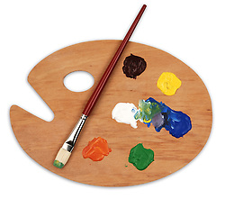 wooden art palette with blobs of paint and a brush on white background with clipping path