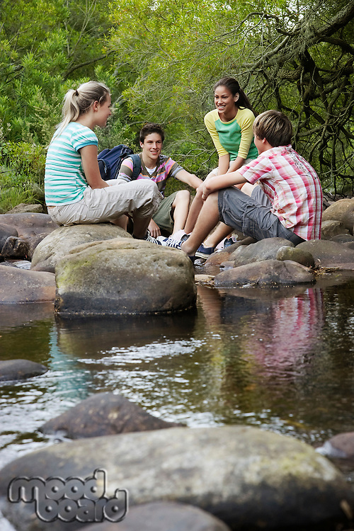 Four teenagers (16-17 years) sitting on stone by river talking