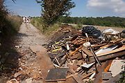 Countryside ramblers and a heap of dumped and burned fly-tipped rubbish on a footpath, on 27th August 2017, near Cobham, Kent, England.