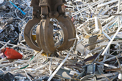 Close up of hydraulic grab machine lifting aluminium ready to be put into the baler machine,