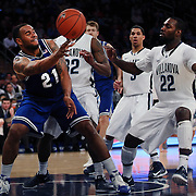 Eugene Teague, (left), Seton Hall, passes while defended by JayVaughn Pinkson, Villanova, during the Villanova Wildcats Vs Seton Hall Pirates basketball game during the Big East Conference Tournament at Madison Square Garden, New York, USA. 12th March 2014. Photo Tim Clayton