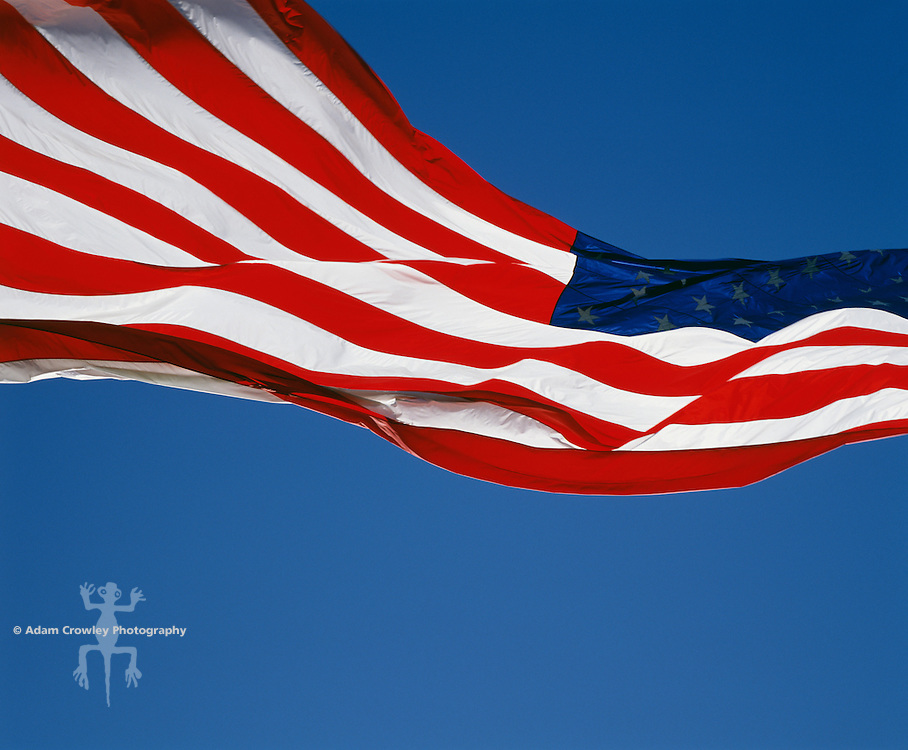U.S. flag flapping against clear blue sky
