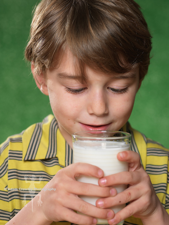 Portrait of boy (7 years old) with missing front tooth, drinking a glass of milk.