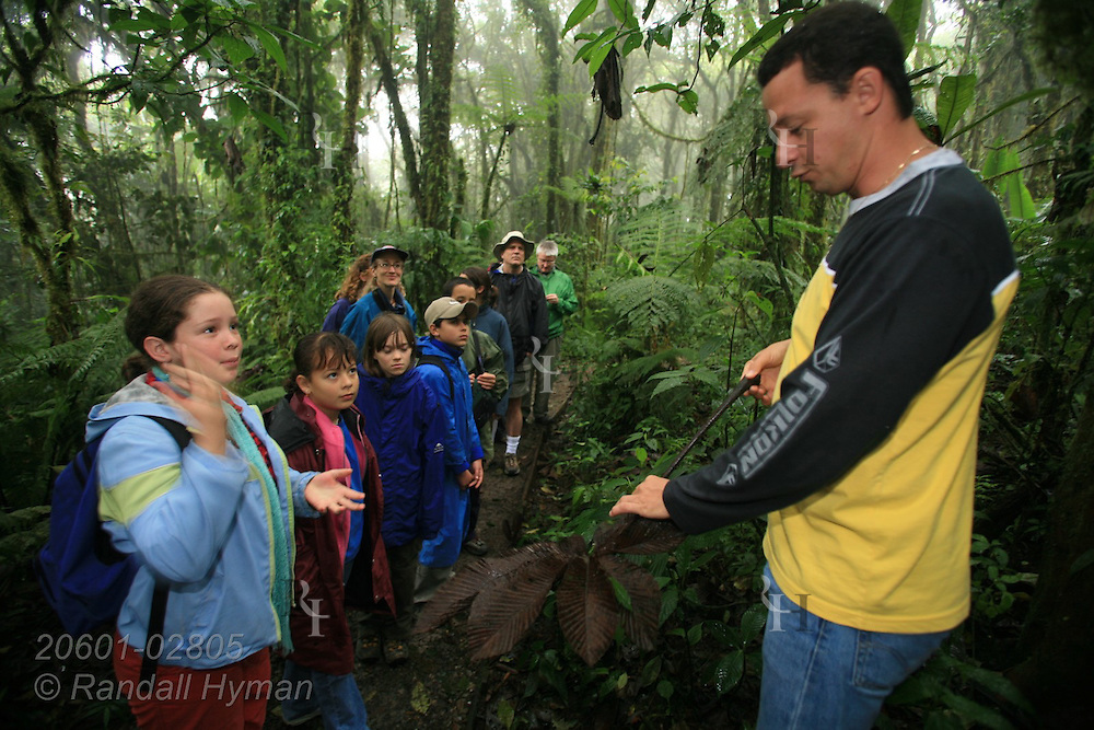 Ecoteach guide Alex Alvarez Rojas leads nature hike in rainforest while Cloud Forest School sixth-grader Jocelyn Mena Mora asks question; Santa Elena National Park, Costa Rica.
