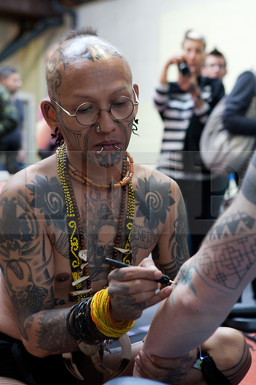 © Licensed to London News Pictures. 28/09/2012. London, UK. An Indonesian tattoo artist draws the tattoo desgin on the arm of a customer. The 8th London Tattoo convention opened today, 28 September 2012 at Tobacco Dock in East London. The convention attracts tattoo artists and body art fans from all over the world and runs until 30 September 2012. Photo credit : Vickie Flores/LNP.