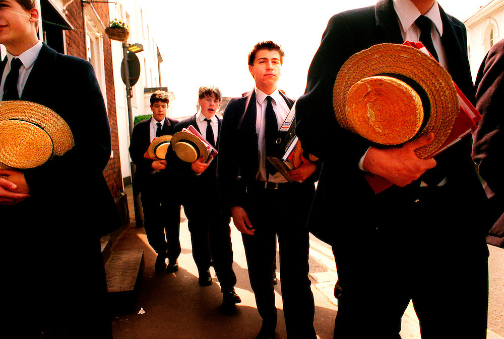 Harrow Schhol boys walk between lessons carrying their books and straw boaters hats