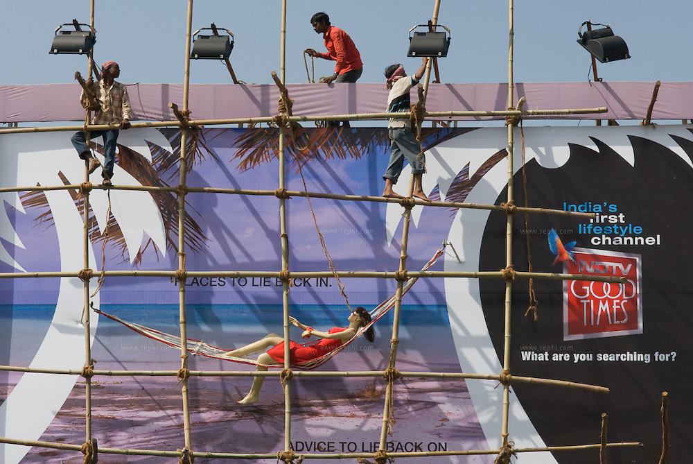 workers use scaffolding to hang a huge billboard on a main road in New Delhi.