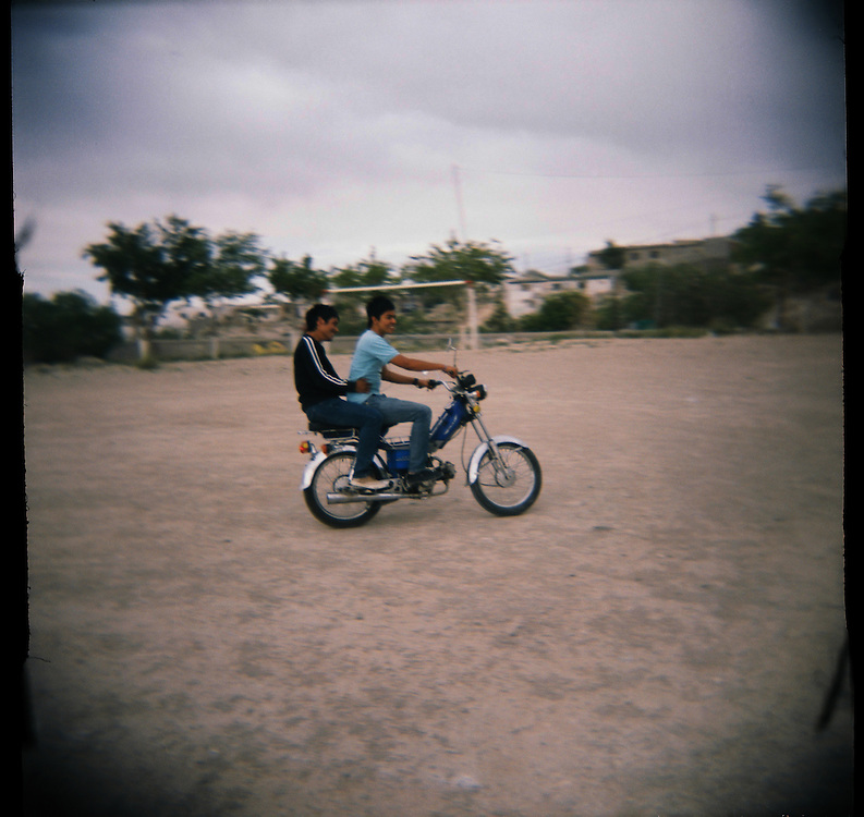 From left, Juan Manuel Delgado, 18, and his friend Gustavo Martinez, 19, ride a motorcycle in the Diaz Ordaz colonia in Ciudad Juarez, Chihuahua Mexico on April 28, 2010. .