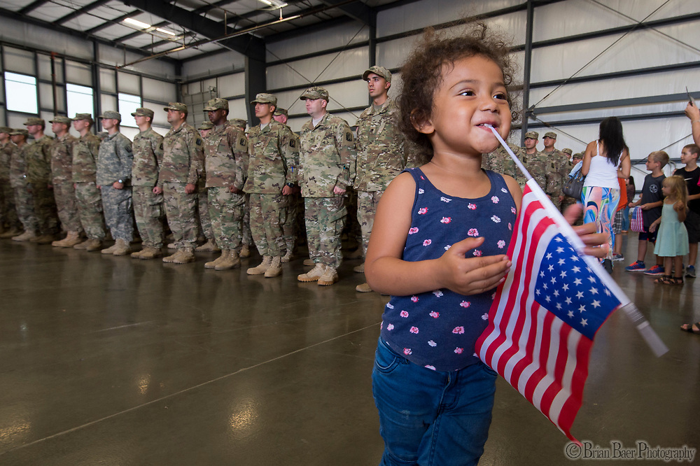 Scarleth Bow (CQ), 2 holds a flag in her mouth as her father Maurice Bow, stands with other members of the California Army National Guard&rsquo;s 1st Battalion, 184th Infantry Regiment, during the deployment ceremony at the International Jet Center at Sacramento Airport,  Saturday Sep 16, 2017. About 300 Soldiers from the California Army National Guard&rsquo;s 1st Battalion, 184th Infantry Regiment, will depart California this weekend for a yearlong training deployment to Jordan in the Middle East. <br /> photo by Brian Baer