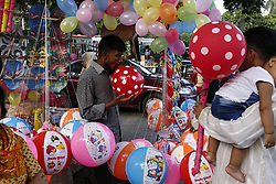 July 21, 2017 - Dhaka, Bangladesh - A street vendor blows a balloon in front of the National Children Park. (Credit Image: © Md. Mehedi Hasan via ZUMA Wire)