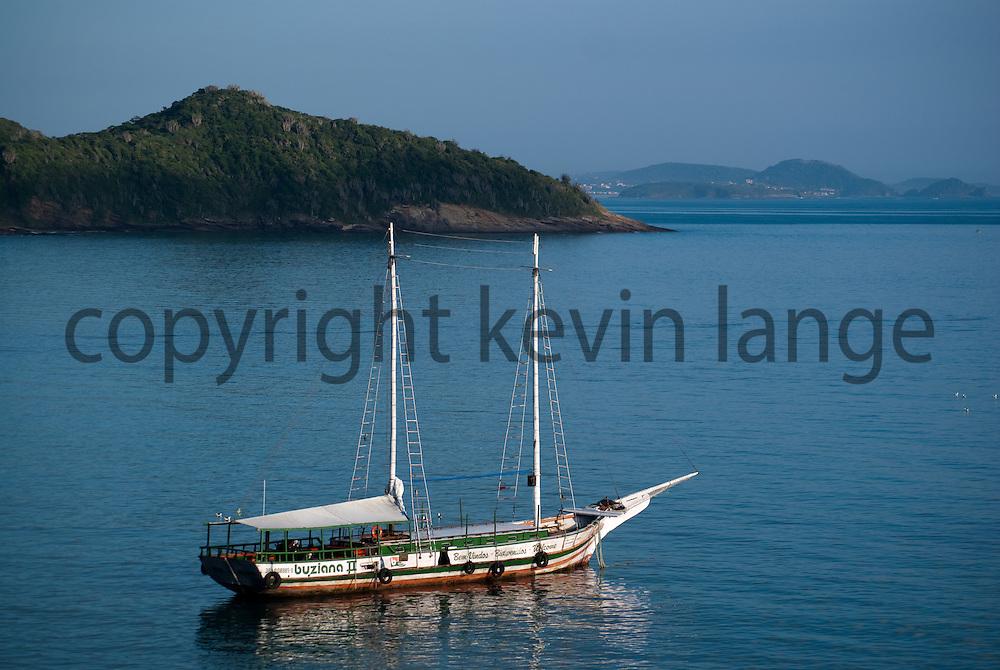 a boat floats in the waters of buzios, rio de janeiro, brazil