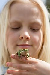 Zelena rega ali bozja zabica (Hyla arborea) / The Little Green Frog in kid's hand, on March 14, 2018 in Ljubljana, Slovenia. Photo by Vid Ponikvar / Sportida