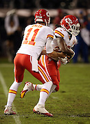 Kansas City Chiefs running back Jamaal Charles (25) takes a first quarter handoff from Kansas City Chiefs quarterback Alex Smith (11) during the NFL week 12 regular season football game against the Oakland Raiders on Thursday, Nov. 20, 2014 in Oakland, Calif. The Raiders won their first game of the season 24-20. ©Paul Anthony Spinelli