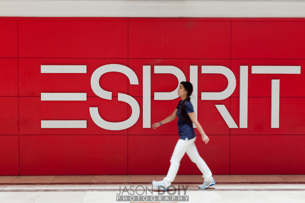 A red Esprit sign and a person walking past.