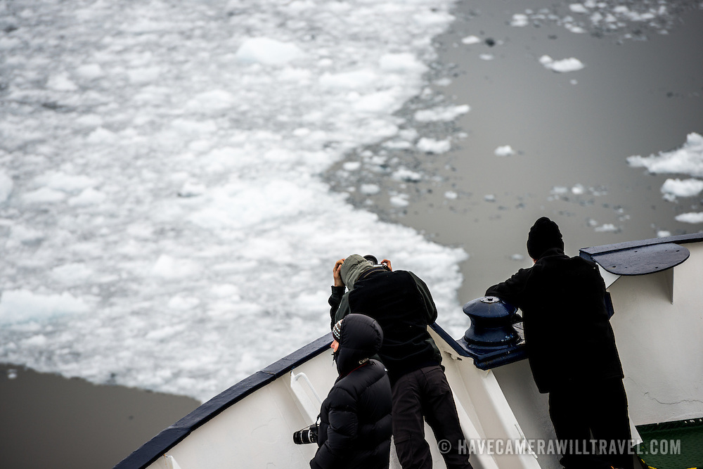 "Passengers stand on the bow of an ice-strengthened Antarctic cruise ship as it navigates the narrow Lemaire Channel on the western side of the Antarctic Peninsula. The Lemaire Channel is sometimes referred to as ""Kodak Gap"" in a nod to its famously scenic views."