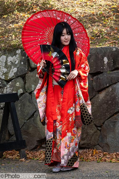 """Costumed Japanese woman with parasol and fan. Matsumoto Castle is a """"hirajiro"""" - a castle built on plains rather than on a hill or mountain, in Matsumoto, Nagano Prefecture, Japan. Matsumotojo's main castle keep and its smaller, second donjon were built from 1592 to 1614, well-fortified as peace was not yet fully achieved at the time. In 1635, when military threats had ceased, a third, barely defended turret and another for moon viewing were added to the castle. Interesting features of the castle include steep wooden stairs, openings to drop stones onto invaders, openings for archers, as well as an observation deck at the top, sixth floor of the main keep with views over the Matsumoto city."""