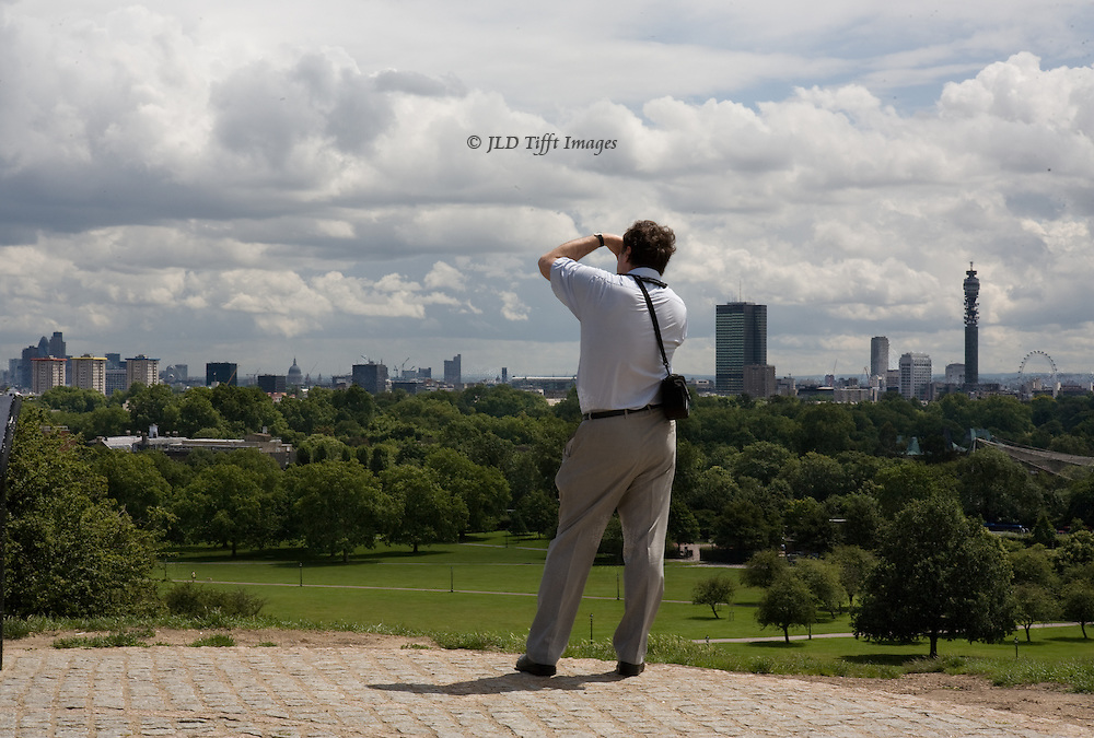 """View of London on the horizon from Primrose Hill.  The city is a visual border between foreground green park land and expansive brilliantly cloudy sky above.  Man seen from the back is near the camera, wearing khakis & white shirt.  He is taking photo in the foreground, camera bag over his shoulder, seen from behind.  Visible but distant landmarks from left to right: the Swiss RE  """"gherkin"""" tower, St. Paul's dome, BBC radio tower, London eye."""