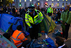 © Licensed to London News Pictures. 09/10/2019. London, UK. Police begin to remove protesters from an Extinction Rebellion roadblock in Parliament Square. Police continue to attempt to clear roads in Westminster on the third day of the protest.  Photo credit: George Cracknell Wright/LNP