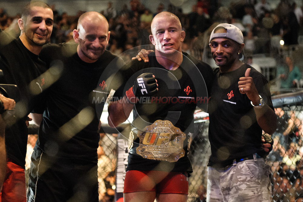 """LAS VEGAS, NEVADA. JULY 11, 2009: (L to R) Firas Zahabi, Greg Jackson, Georges St. Pierre and Phil Nurse pose for photographers after St. Pierre successfully defended his UFC welterweight title during """"UFC 100: Making History"""" inside the Mandalay Bay Events Center in Las Vegas, Nevada."""