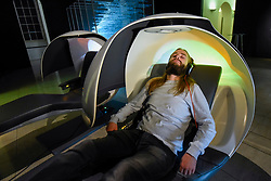 "© Licensed to London News Pictures. 29/10/2019. LONDON, UK. A staff member experiences ""MetroNaps EnergyPods"".  Preview of ""24/7: A Wake-Up Call For Our Non-Stop World"", a new exhibition opening on 31 October at Somerset House.  The show examines our inability to switch off from our 24/7 culture.  Over 50 multi-disciplinary works explore the pressure to produce and consume information around the clock. taking visitors on a 24-hour cycle from dawn to dusk through interactive installations.  Photo credit: Stephen Chung/LNP"