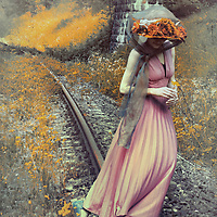 A woman  in a pink flowing dress, blue shoes and a red flowery hat, holding a little yellow flower & crossing a railway on a sunny day.