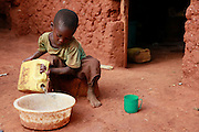 Jean Damacene pours water to wash dishes at home.  Gatora village, Bugesera district. Rwanda...Picture: WaterAid / Zute Lightfoot