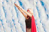 Young woman in superhero outfit taking a leap in the air against cloudy sky