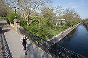 UNITED KINGDOM, London: 09 April 2020 <br /> A jogger runs across a bridge over Regent's Canal as the sun shines this afternoon. Temperatures for Easter weekend are set to reach 24C degrees, with a reminder to the public to save lives and help the NHS by staying indoors.